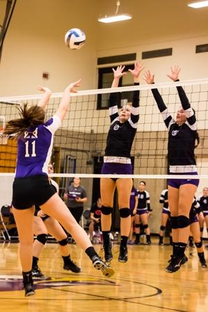 Freshmen Lindsay Gerding  (from left) and Syd Walker go for a block against Lincoln in the Eagles first home game.