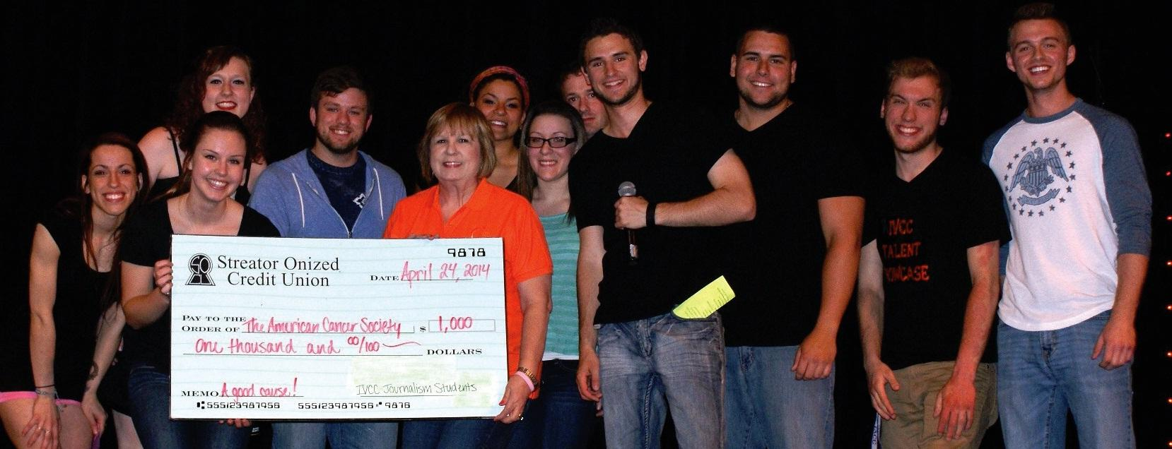 Hailey Shan (back, from left), Christiana Johnson, Brandon Miller; (front) Jade Atkinson, Andrea Neff, Cody Zton, Nancy Jackson, Julianne Cameron, Philip Denner, Alex Danko, Tomasz Augustyniak and Cody Bornemann award the check with the fund raising total at the end of the IV Talent Showcase on April 24. The Journalism 1002 class raised more than $1,000 for the American Cancer Society and presented the check to Jackson from the Relay for Life, American Cancer Society.