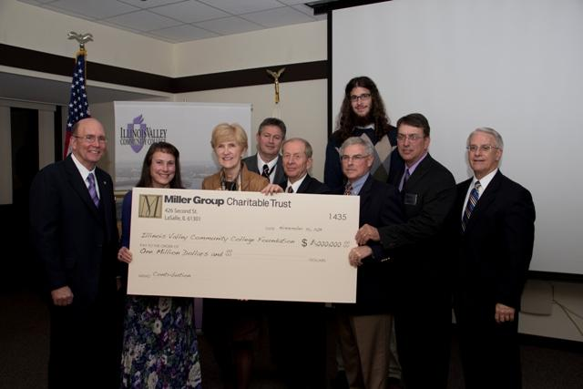 College administrators and trustees receive a giant check from Joyce McCullough and Cathy Miller of the Miller Group Charitable Trust.