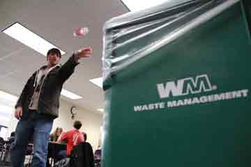 """A students tosses an item into the new recycling bins on campus. The IV Sustainability group has helped to change IVCC's recycling system to a new """"single-stream recycling"""" system provided by Waste Management."""
