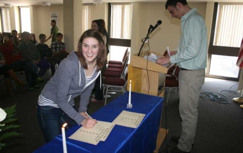 Kristina Werner of Streator signs the Phi Theta Kappa log as Braiden Skinner, Rho Omega vice president for membership, introduces new members at the March 28 afternoon induction ceremony.