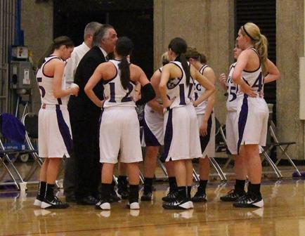 The Lady Eagles gather around first-year coach Tom Ptak during a timeout in the team's 78-72 victory on Jan. 16 over Carl Sandburg College.