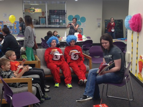 Chelsea Berg (right) reads a story as part of the games and activities for Dr. Seuss' birthday event March 3 in the cafeteria as Thing 1 & 2 (Aubrey Molln and Mack Borio) look on.