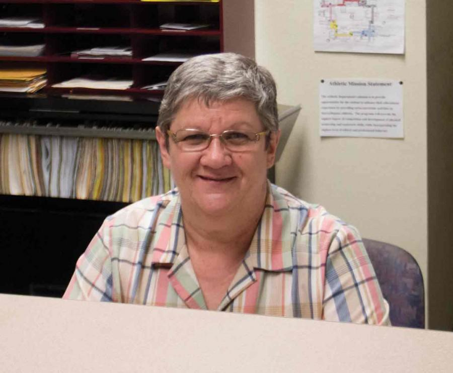 IVCC Administrative Assistant Sue Harding flashes her trademark smile which always greets students in the IVCCgymnasium.
