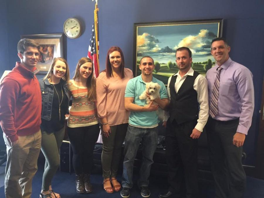 IVCC PTK members (from left) Travis Sauers, Nicole Stevenson, Monica Leonard, Kaitlin Raineri, Trevor Finnan, Brandon Miller and faculty advisor Eric Schroeder pause to play with Magpi (held by Finnan) in U.S. Rep. Adam Kinzinger's office. Members of IVCC's Rho Omega chapter of Phi Theta Kappa had a meet and greet with Kinzinger's staff during their recent trip to Washington D.C. for the PTK national convention.  The group spoke with Kinzinger's staff members about education, retirement, immigration and reaching across party lines.