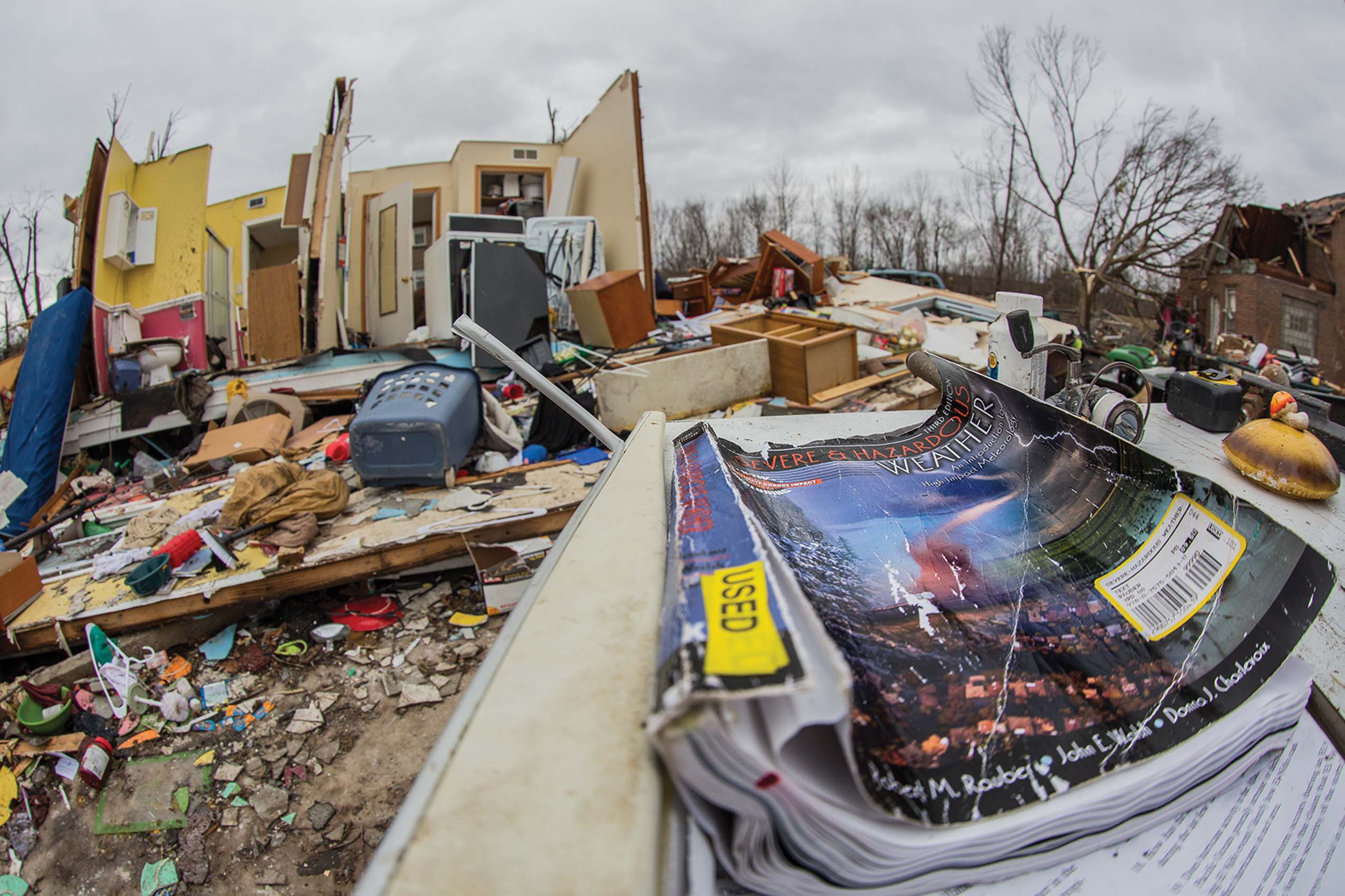 A book on tornadoes and other disasters (top photo) lies outside a damaged house in Naplate after the Feb. 28 storms.