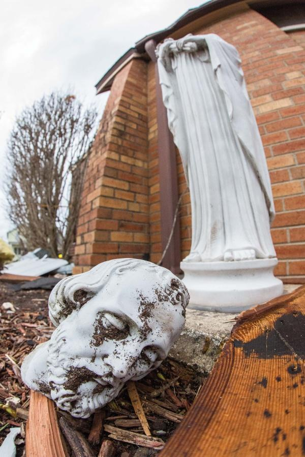 The head of a statue of Christ appears to cry thanks to a streak of dirt under his eye as a result of the storm.
