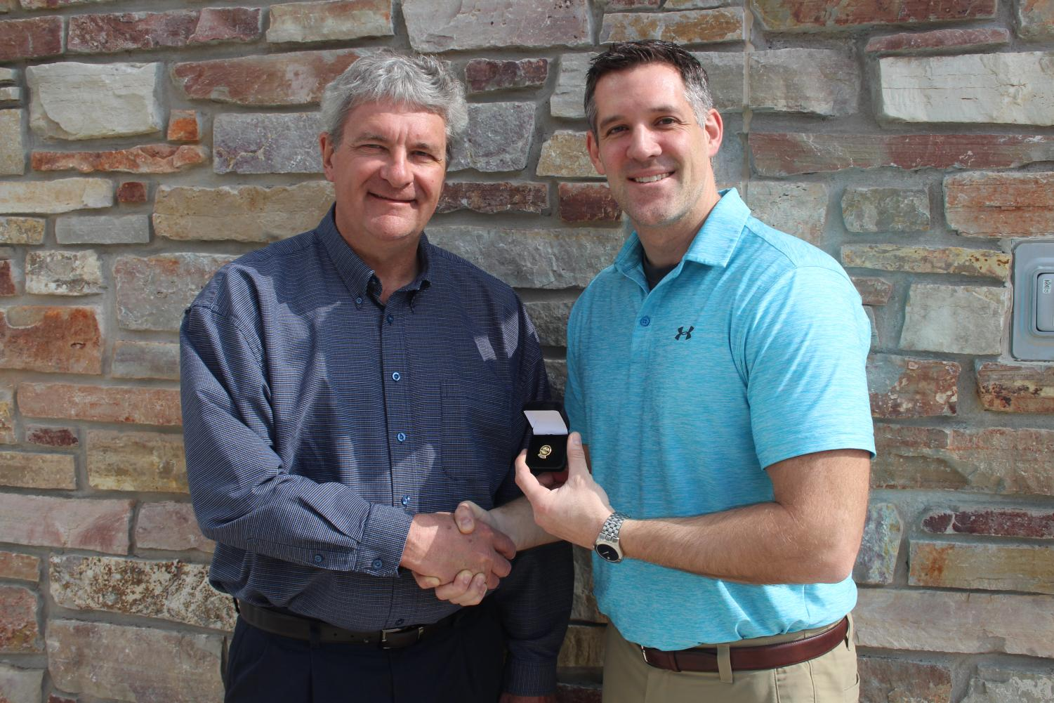 Thanks for the service Dean of Natural Sciences and Business Ron Groleau (left) presents IVCC biology instructor Eric Schroeder (right) with a lapel pin in recognition of his service to Phi Theta Kappa.