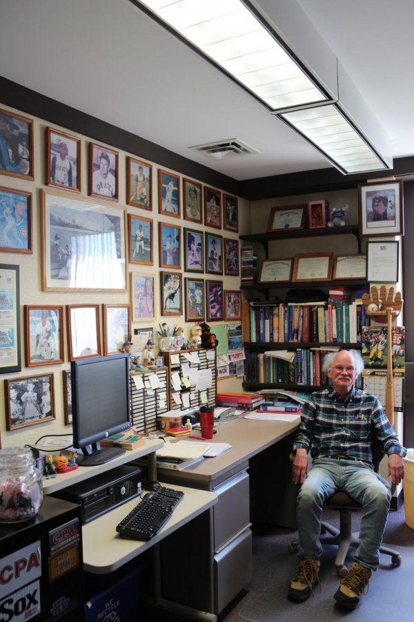 Retiring accounting professor Mike Sankovich sits in his office surrounded by his other passions: movie and baseball memorabilia and music.