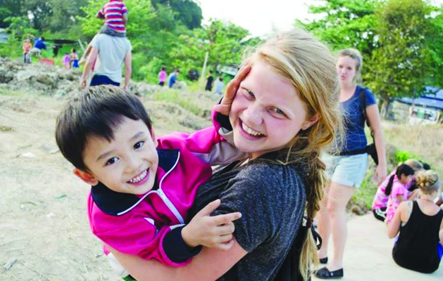 Hannah Munson plays with Thai children on a makeshift soccer field where YWAM bonds with locals.